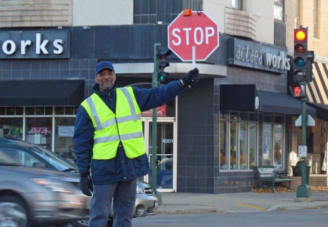 Crossing Guard holding a stop sign on a city street