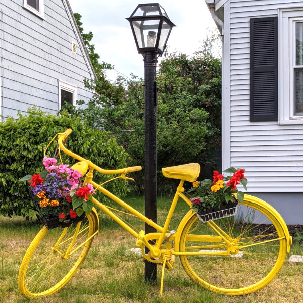 Yellow bike with flower basket leaning on a pole